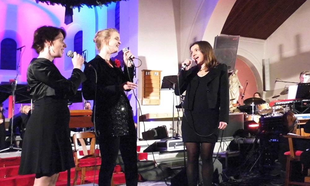 Dirigente Janet van Gaalen-Schouten (midden) zingt samen met twee koorleden solopartijen.