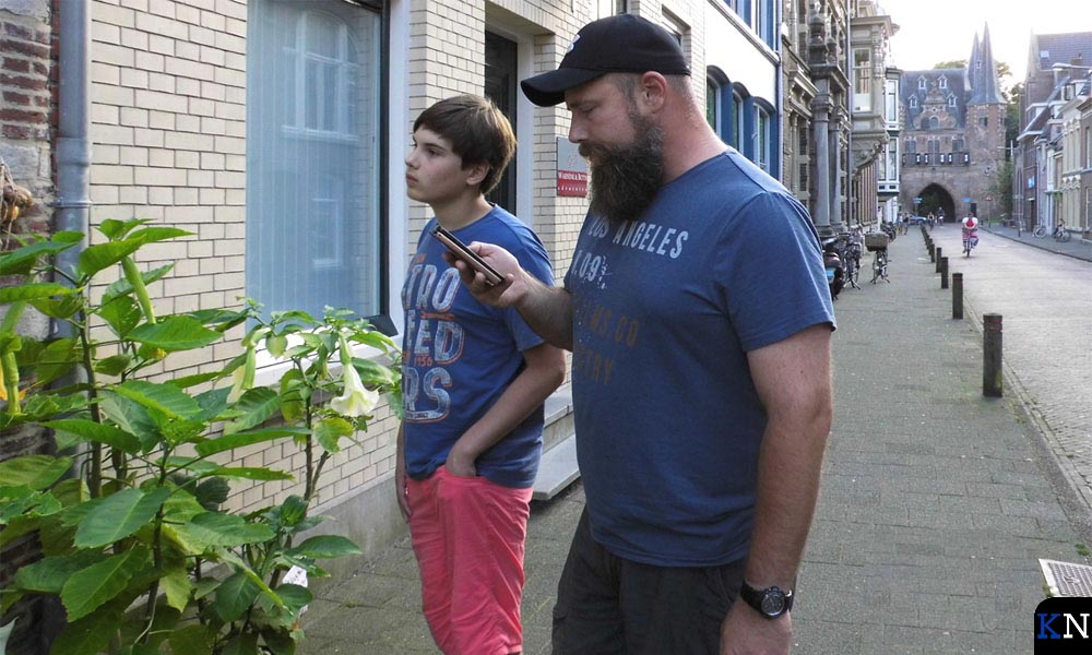Daniël en Henk kijken of ze bij een juiste gevel staan.