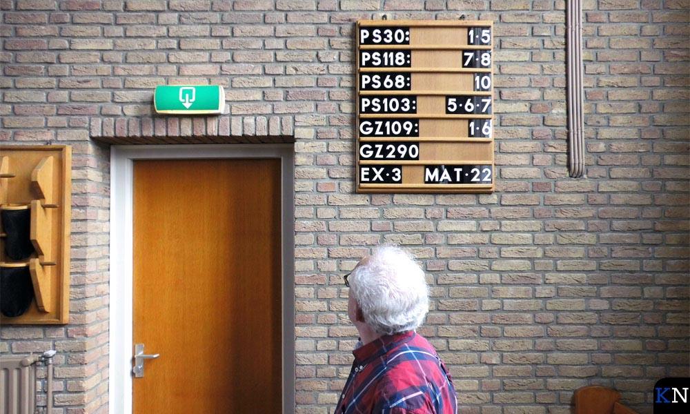 De koster van de NH Kerk in Grafhorst controleert het liederenbord.