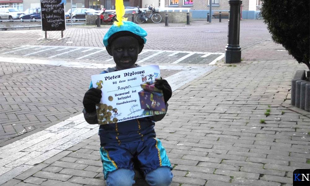 Rayan toont trots het Pietendiploma dat hij heeft gehaald bij het Sinterklaashuis.