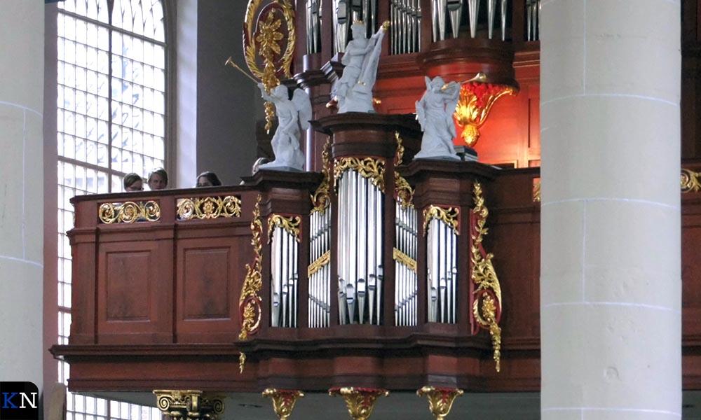 Verscholen op de balustrade van het orgel bracht de Cantorij van de TUK haar gezangen ten gehore.