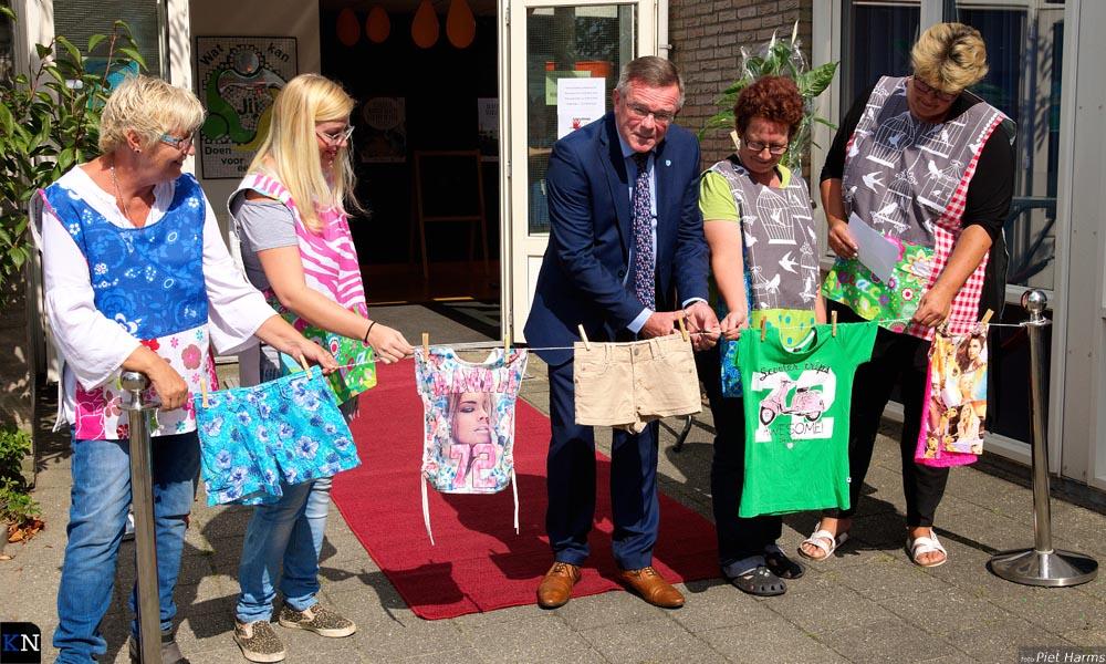 Samen met vrijwilligers knipt wethouder Veldhoen het lint door waarmee de Weggeefschuur is geopend.