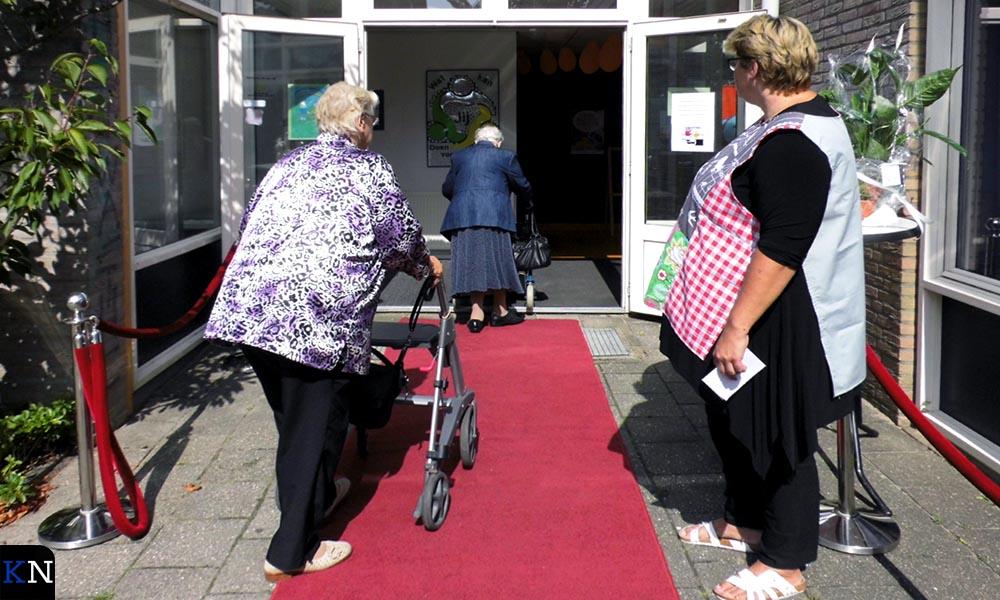Enkele buurvrouwen van belendende zorgwoningen komen de Weggeefschuur welkom heten.