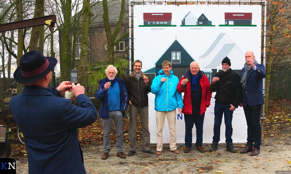 Burgemeester Koelewijn legt de gebruikers van de Koggewerf vast voor het bord onthuld als start van de bouw van de botenloods.