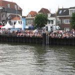 Vanaf de IJsselkade kijkt het publiek toe.