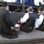 Drie straatmuzikanten stellen zich bescheiden achter de schermen op.