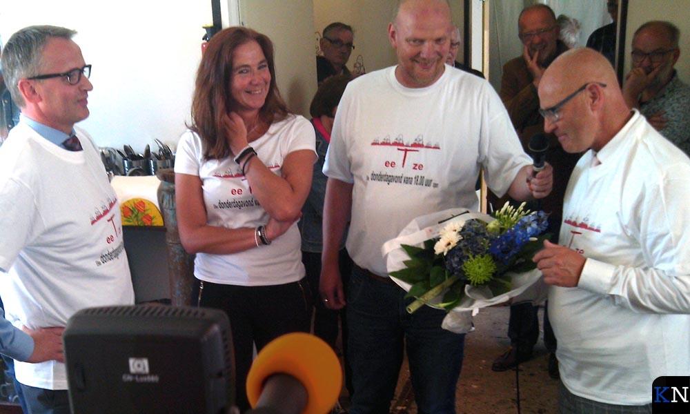 Gea en Jaap krijgen een bloemetje overhandigd bij de opening van eeTze.