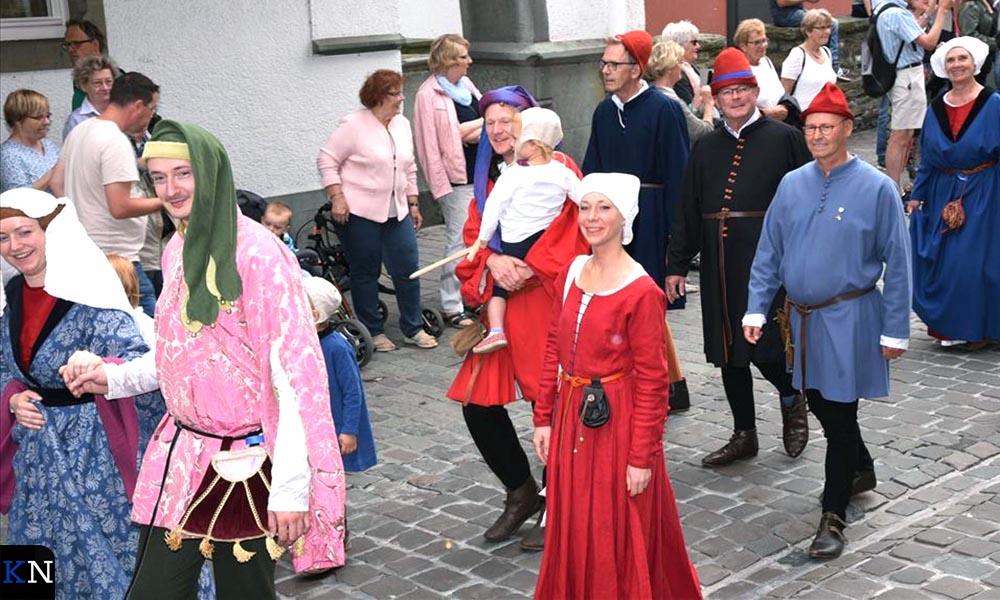 Achter de dame en heer in het rood lopen (v.r.n.l.) schout Koelewijn, schepen Veldhoen en klerk Goedegebure.