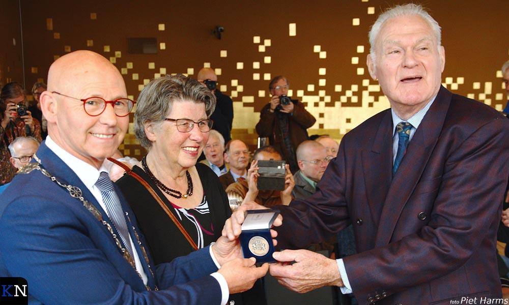 Kees Schilder toont verguld de Zilveren Legpenning van de gemeente Kampen.