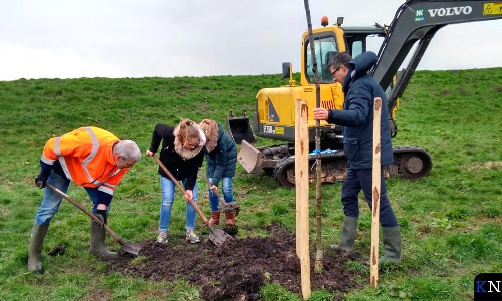 Wethouder Jan Peter van der Sluis assisteert de leerlingen bij de aanplant van de notenbomen.