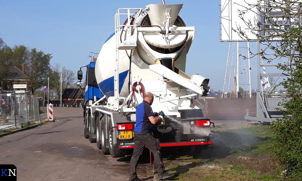 Na het beton storten wordt de vrachtwagen schoon gespoten in de berm.