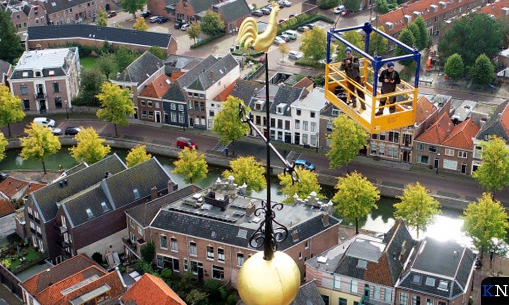 De opgefriste bol en haan worden teruggezet op de toren van de Bovenkerk in Kampen.