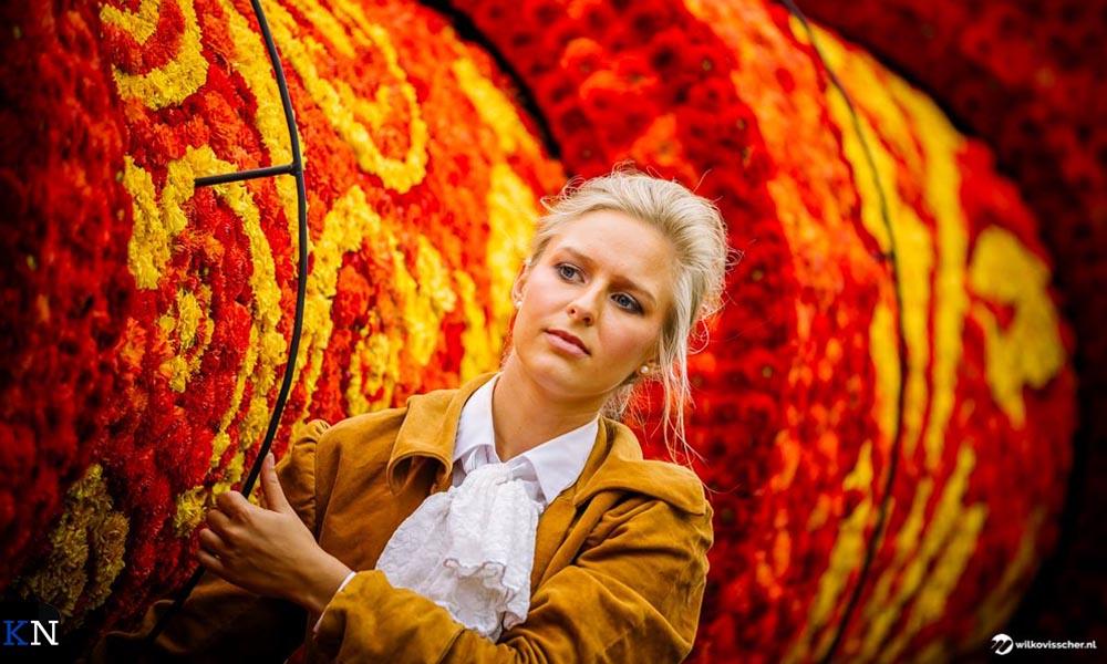Een deelneemster aan het bloemencorso in Sint Jansklooster ondersteunt haar creatie.