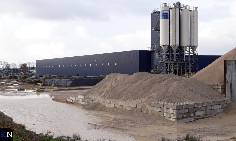 Tussen fabriekshal en zandopslag ligt het bassin waarin water wordt opgevangen.