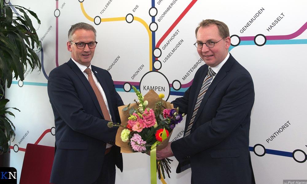 Henk Jan Bart (r.) neemt de felicitaties en bloemen in ontvangst van Eibert Spaan.