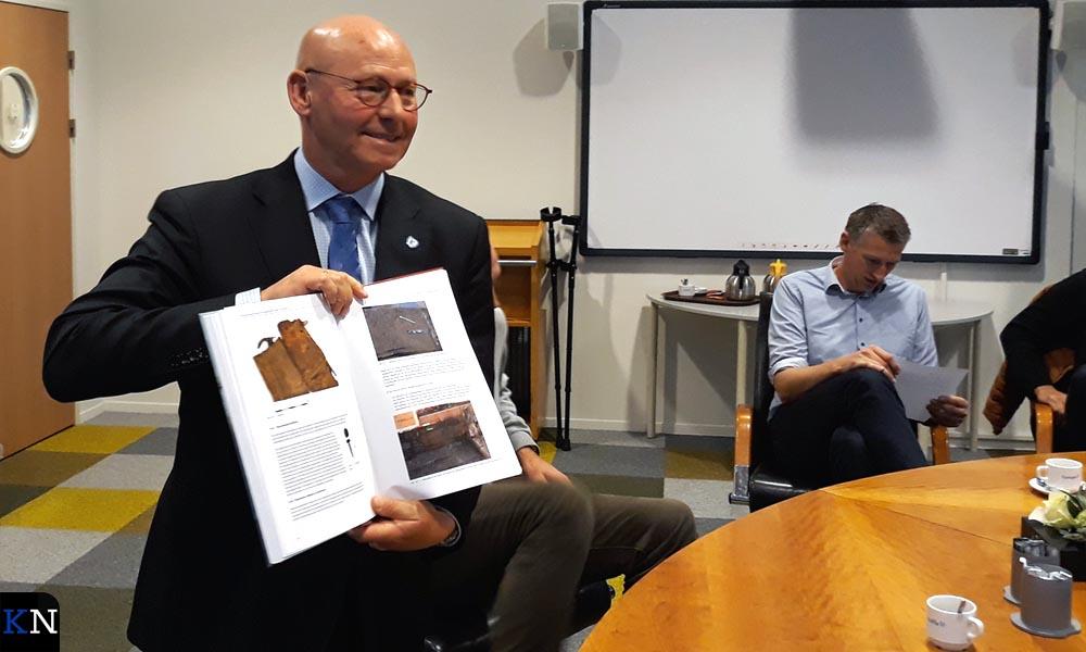 Burgemeester Koelewijn toont het boek van Wouter Waldus over de IJsselkogge.