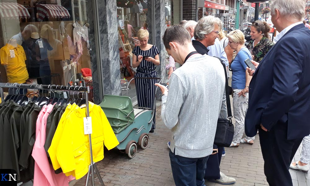 Bij een kinderzaak in de Oudestraat staat een ouderwetse kinderwagen.