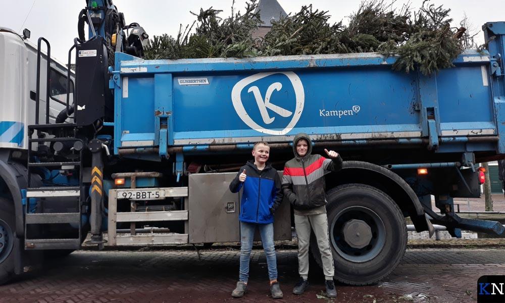 Een trotse Kenny en Mike voor de vrachtwagen met hun opgehaalde kerstbomen.
