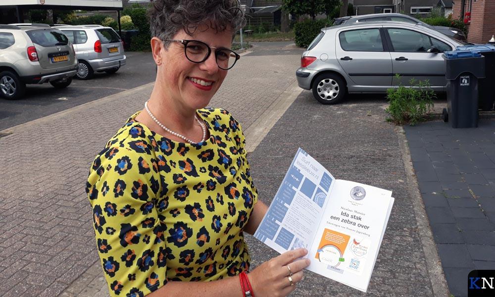 Marjolijn Dijkstra toont één van de Kinderzwerfboeken uit haar Station aan de Sterrekroos.