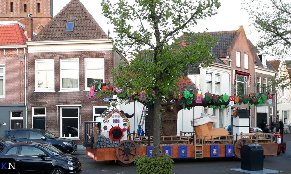 Een praalwagen met een boom rijdt achter een boom naar de start voor Lampionoptocht.
