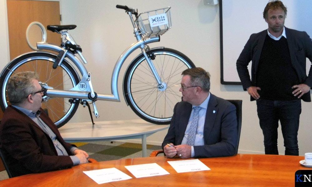 Directeur, wethouder en ontwerper (v.l.n.r.) presenteren de deelfiets van Kris-Kras.