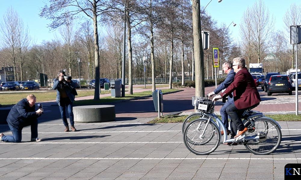 Wethouder en directeur demonstreren de deelfietsen voor de fotografen.
