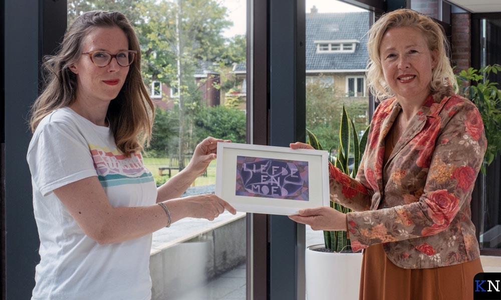 Kim van Norren overhandigt een troostend kunstwerkje aan de directrice van IJsselheem.