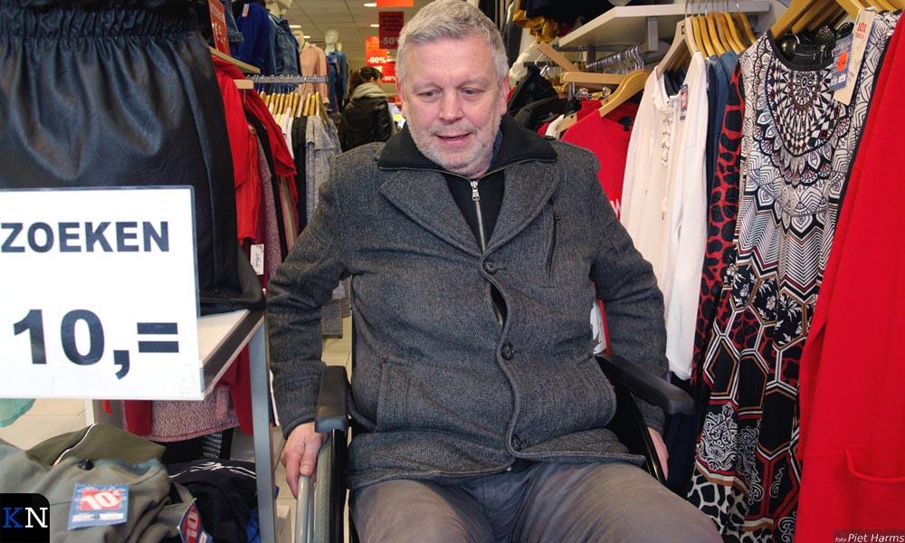 Nardus wringt zich per rolstoel tussen de uitgestalde kleding door.