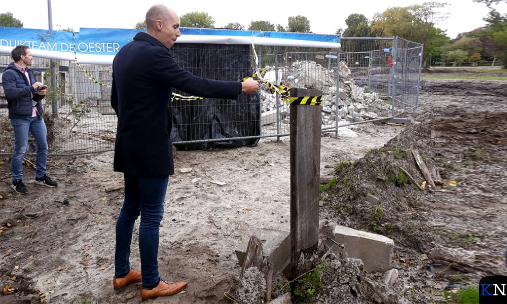 Wethouder Geert Meijering knipt het lint door waarop twee grote spandoekn zich ontrollen.