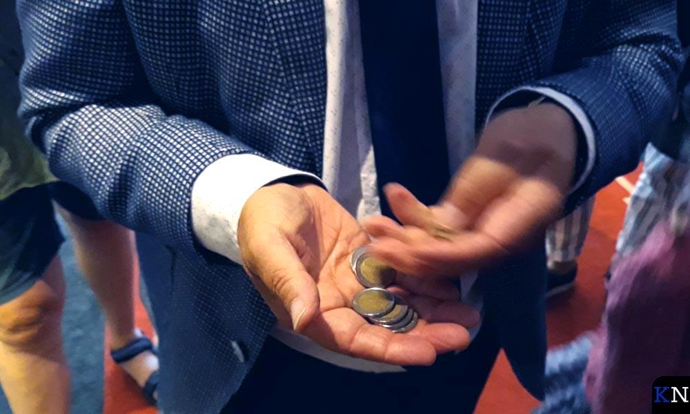 Burgemeester Koelewijn telt zijn twee-Euro-muntstukken.
