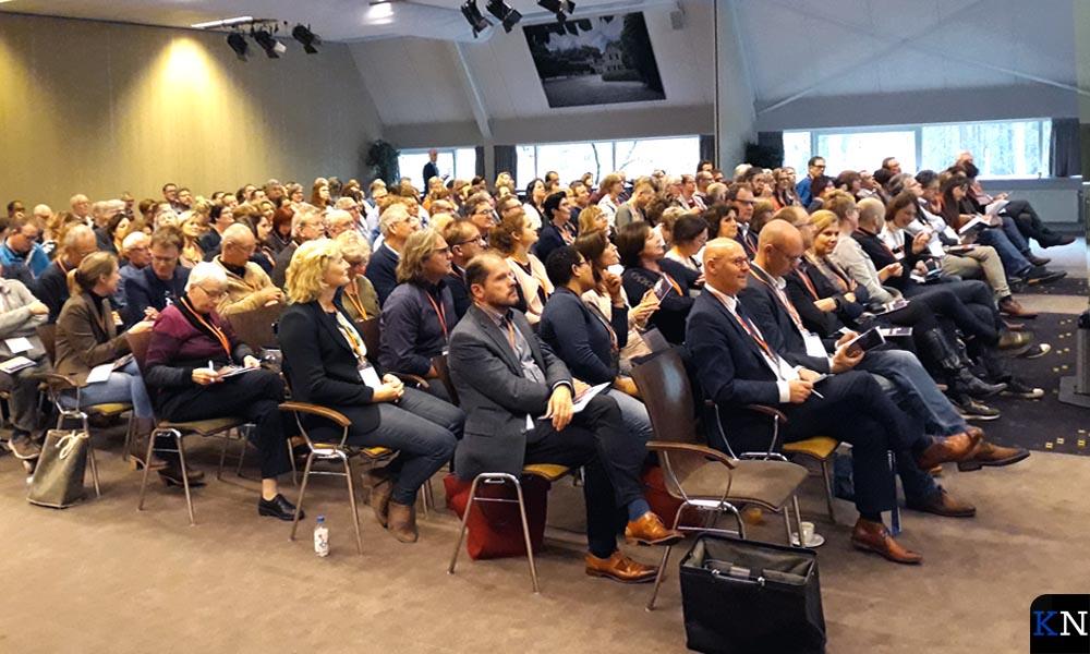 Alle aanwezigen met op de eerste rij burgemeester Koelewijn en op de derde rij het bestuur van Present Kampen.