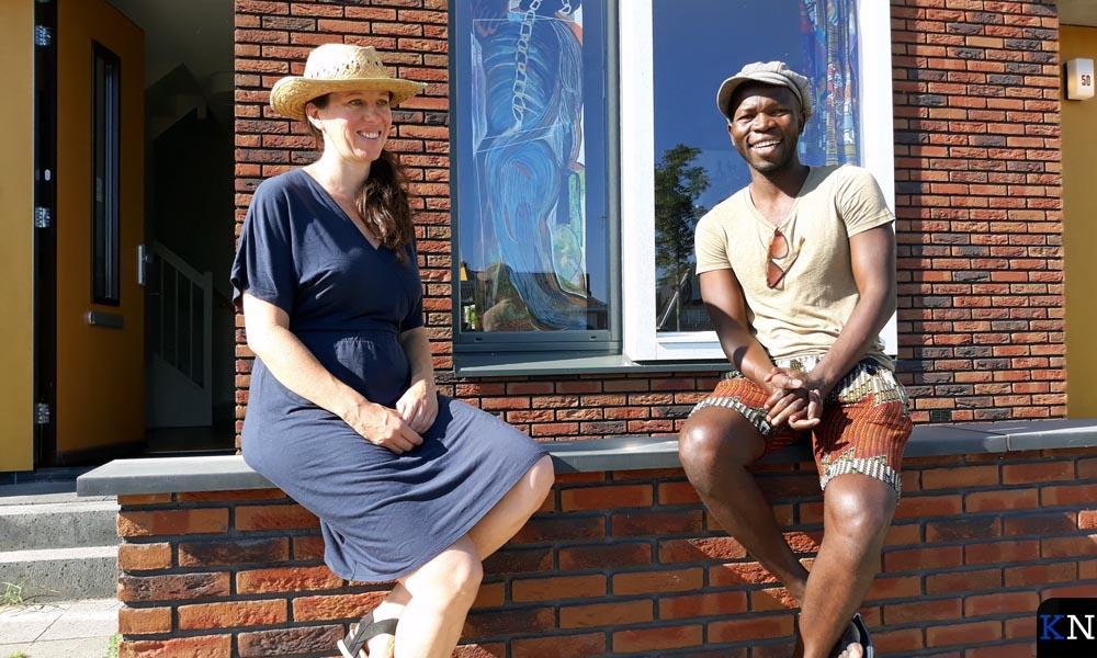 Maaike Cotterink en Alioune Diagne voor hun huis met een voorproefje van hun coronacultuursnelloketproject 'Raamwerk'.