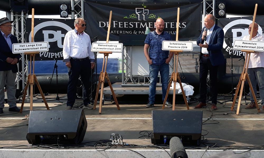 De naamgevers van de kunstwerken in het Reevediep verzamlden zich op het podium met gedeputeerde Bert Boerman.