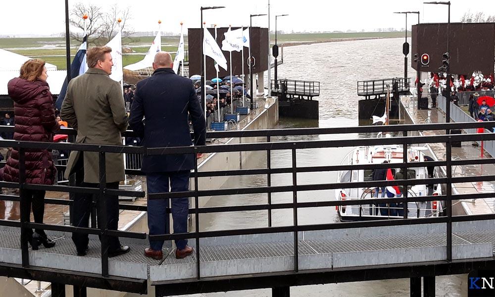 Koning Willem-Alexander opent de sluis geflankeerd door gedputeerde Bert Boerman en minister Cora van Nieuwenhuizen.