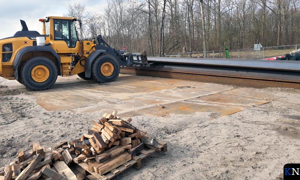Een bulldozer verplaatst de damwanden.