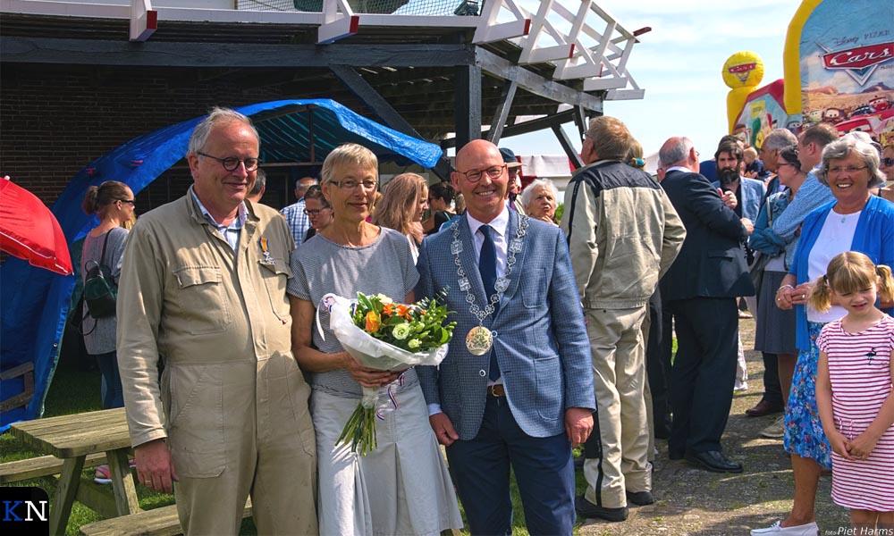 De koninklijk onderscheiden molenaar Sjaak Poot poseert samen met zijn vrouw en de burgemeester.