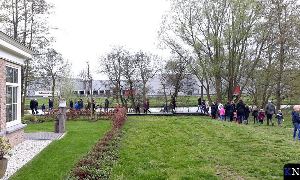 Bewoners en (school)kinderen lopen van het feest naar het bruggetje.