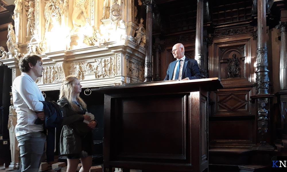 Burgemeester Koelewijn toont Kevin en Karlijn de Schepenzaal in het Oude Raadhuis.
