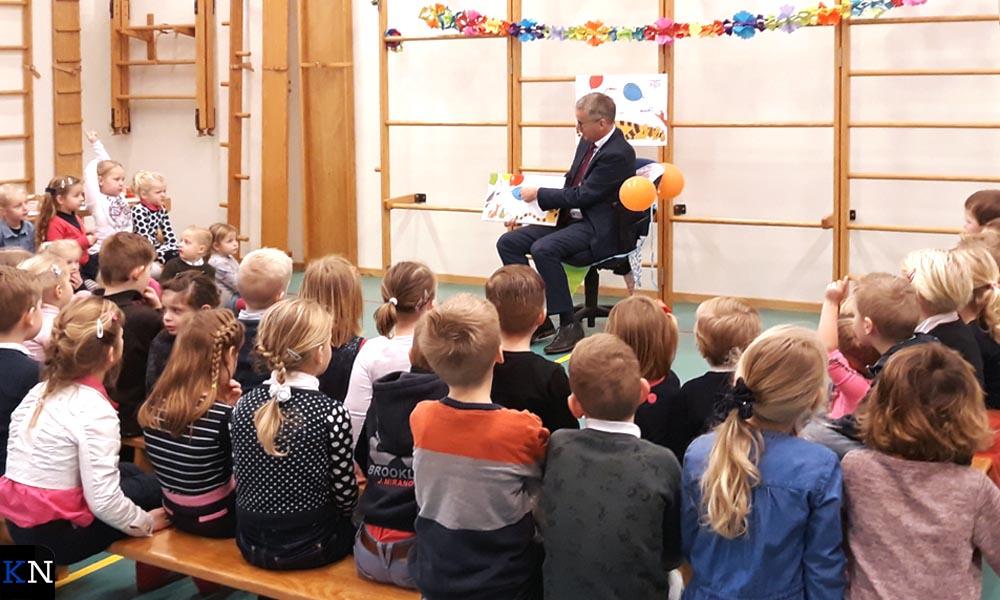 """Kinderen van School met de Bijbel 'Het Visnet' in Grafhorst luisteren stil naar de """"meneer van de gemeente""""."""