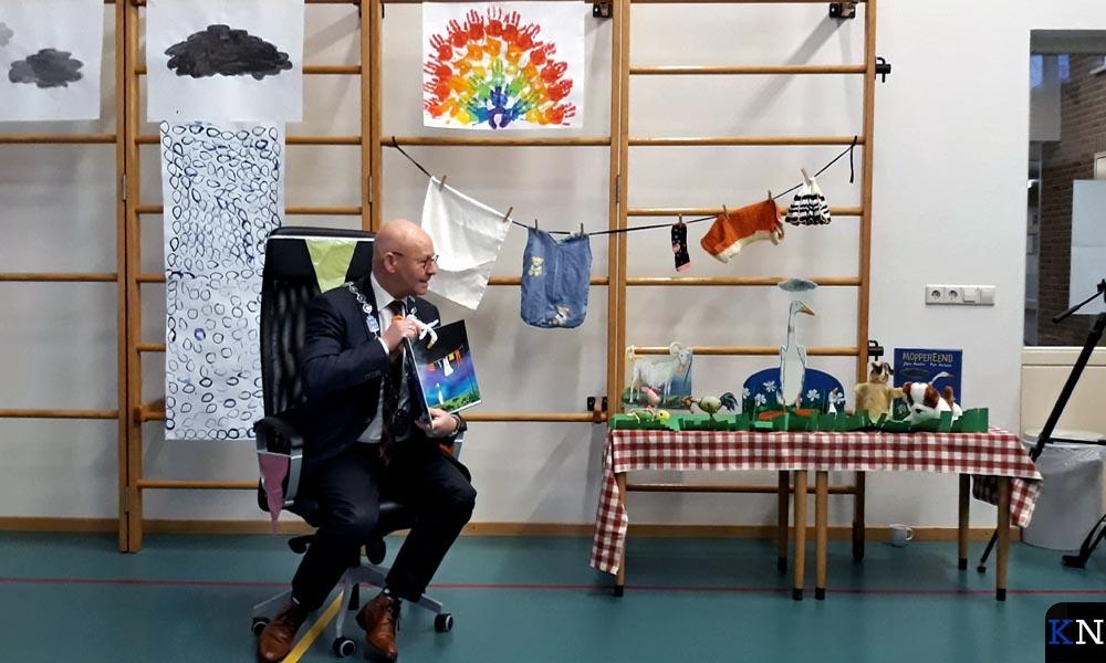 Burgeemster Koelewijn leest in interactie met de kinderne voor uit Moppereend.