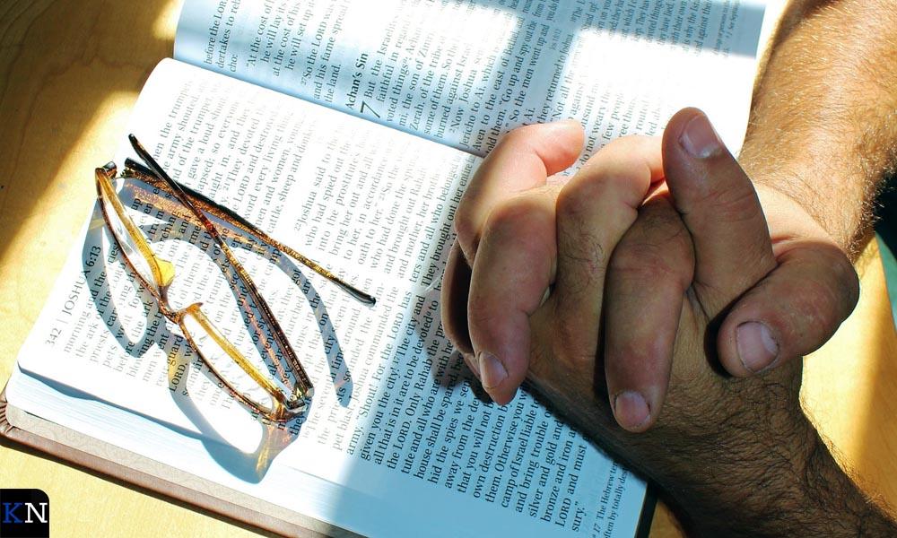 Bidden boven een geopende Bijbel.