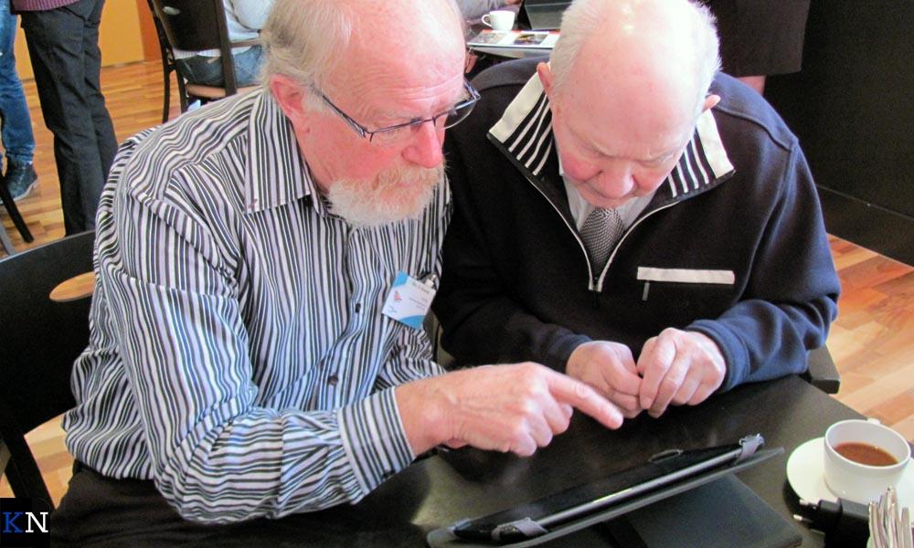 Senioren helpen elkaar om te gaan met de iPad.