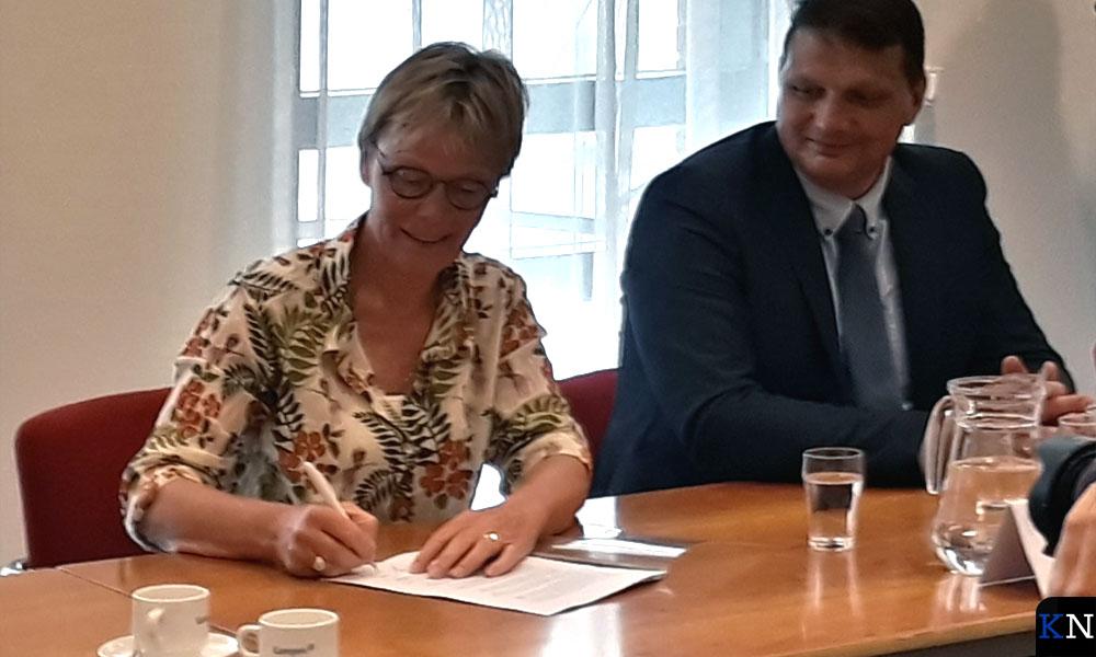 Nieke Jansen ondertekent het coalitieakkoord met de titel 'Nieuwe energie'.