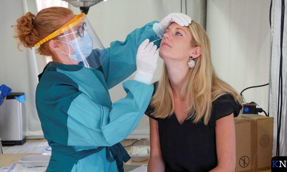 Een medewerkster van GGD IJsselland test een verkouden persoon.