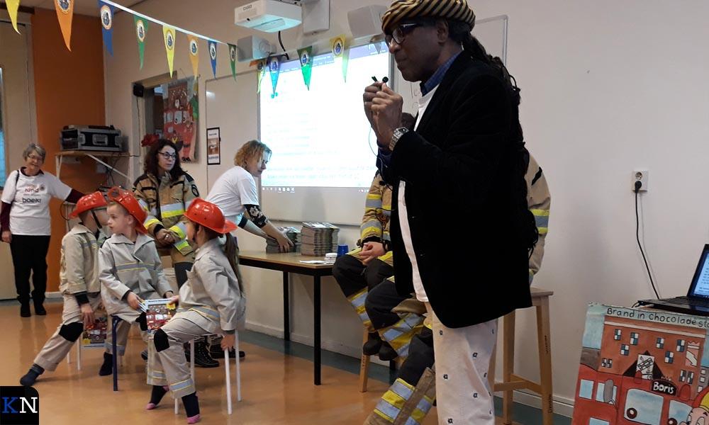 Lesly Reiziger leest samen met de kinderen het brandweerboek.