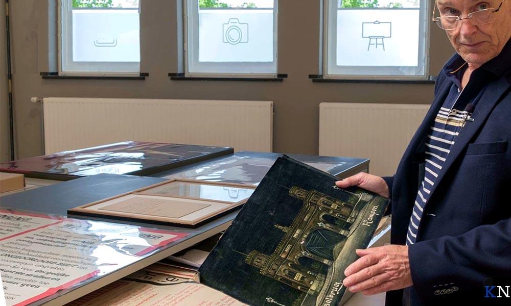 Herman Harder toont een door een granaatscherf beschadigde foto van de Kamper Stadsbrug.
