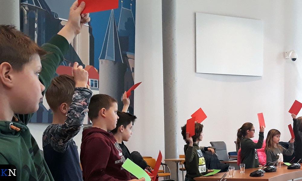 Leerlingen van CBS De Regenboog stemmen in de raadszaal tijdens een kwis.