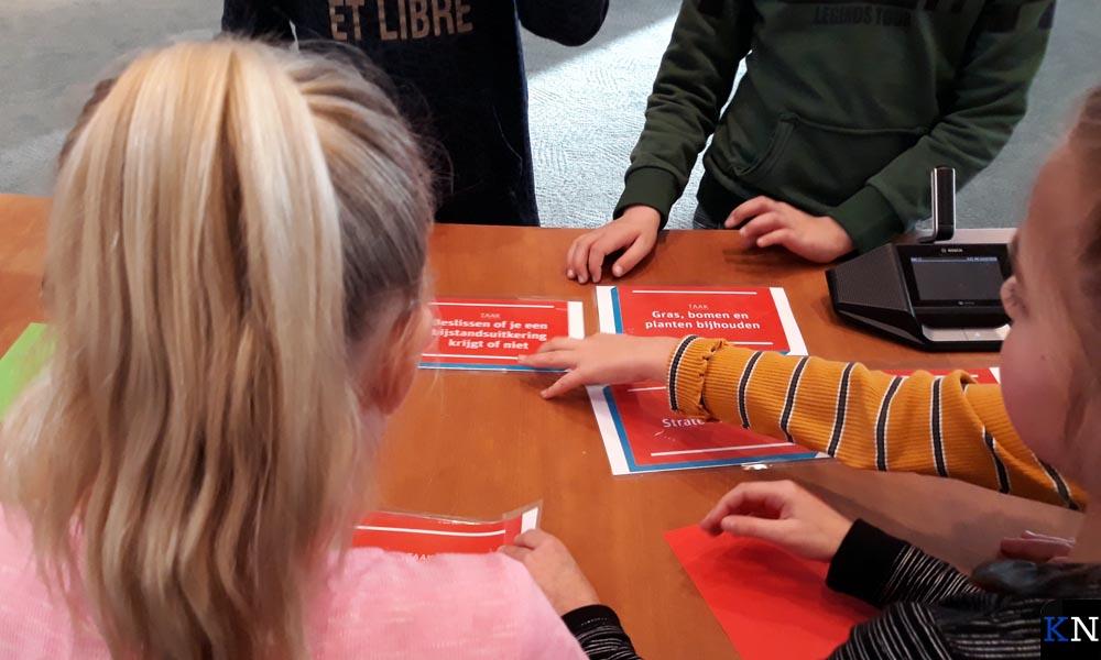 Leerlingen van CBS De Regenboog buigen zich in de raadszaal over stellingen.