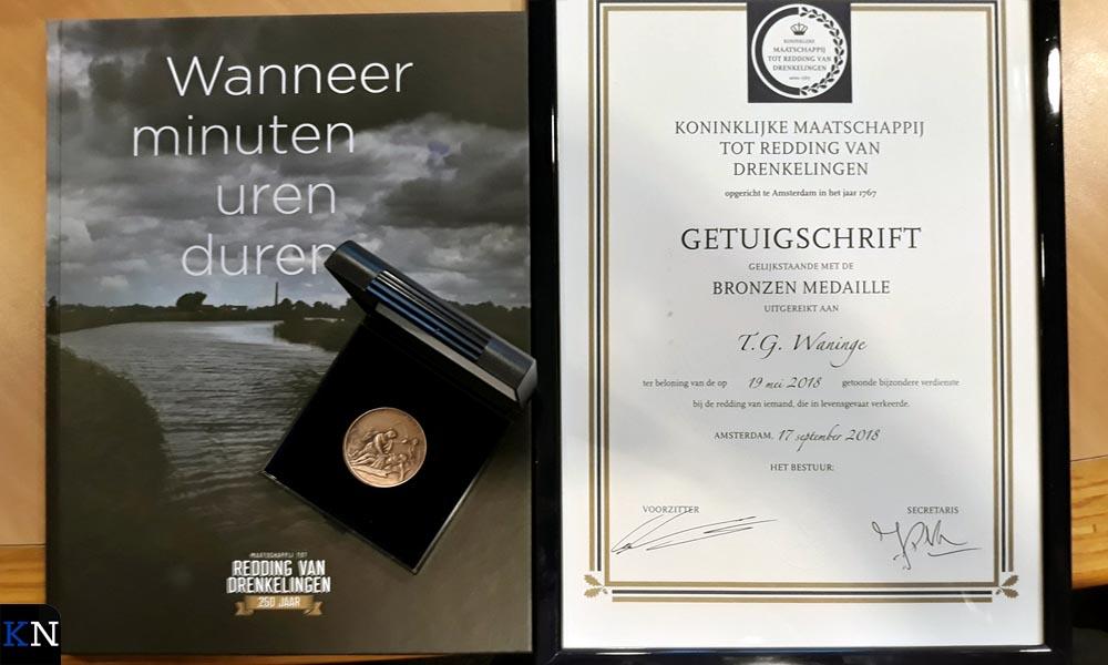 Het getuigschrift , het jubileumboek van de KMRD en de bronzen medaille die Tim Waringe ontvangt.