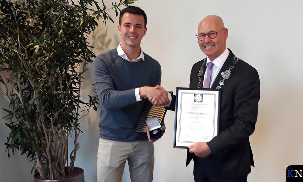 Tim Waninge ontvangt het certificaat en de bronzen medaille van burgemeester Koelewijn.